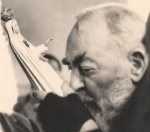 Padre Pio kissing a statue of the Blessed Mother